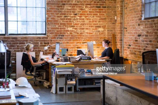 Two women sitting across from each other in architect office