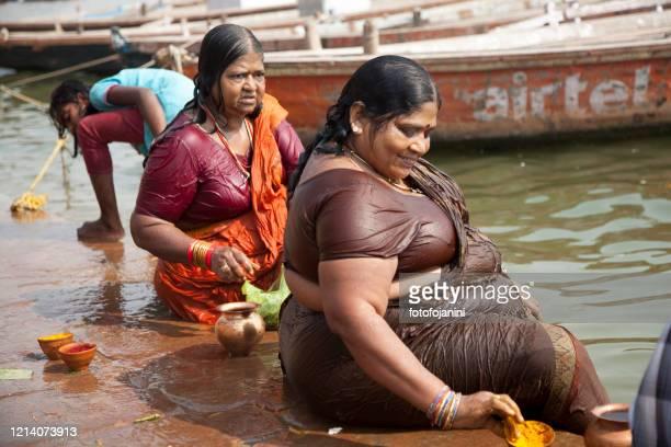 バラナシのガンジ川沿いに座っている2人の女性 - fotofojanini ストックフォトと画像