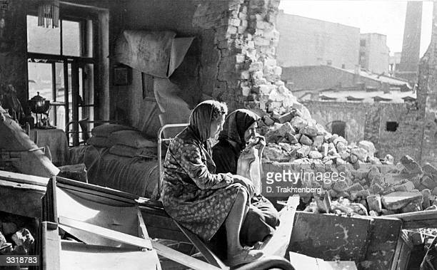 Two women sitting among the debris in the aftermath of the German bombardment of Leningrad Trying to compel the Russian defenders to surrender the...