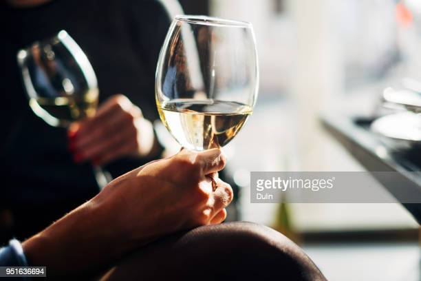 two women sitting at a table enjoying a glass of wine - white wine stock pictures, royalty-free photos & images