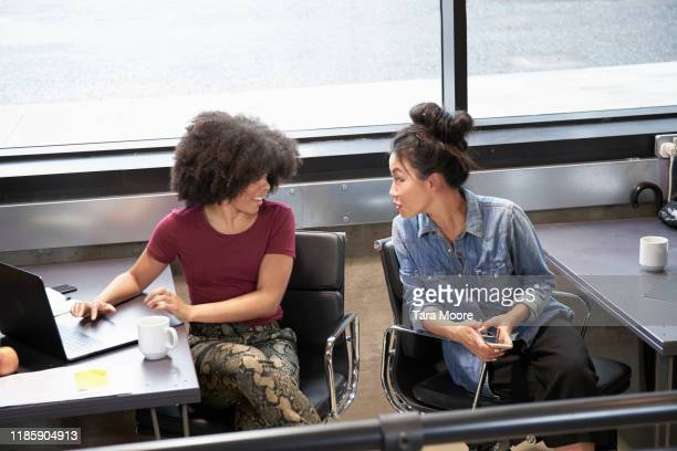 two women sitting at desks working on computers - rumor stock pictures, royalty-free photos & images