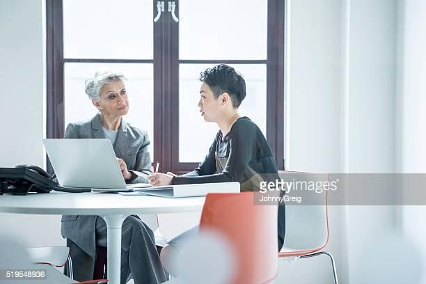 Zwei Frauen sitzen an einem Tisch in modernen Büro