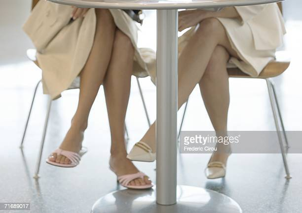 two women sitting at table, view of legs under table - under skirt stock photos and pictures