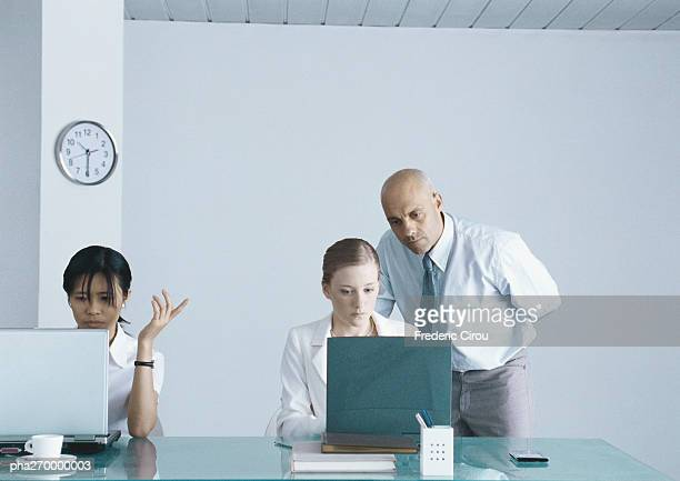 Two women sitting at table with laptops, businessman looking over shoulder of one woman