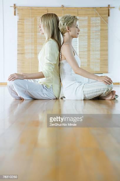 Two women sitting back to back, meditating