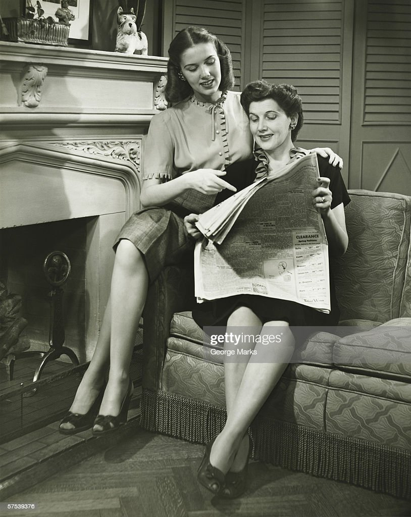 Two women sitting by fireplace, reading newspaper, (B&W) : Stock Photo