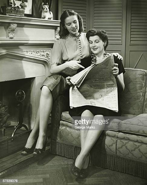 Two women sitting by fireplace, reading newspaper, (B&W)