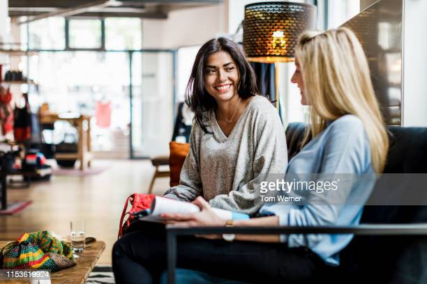 two women sitting down taking a break from shopping - female friendship stock pictures, royalty-free photos & images