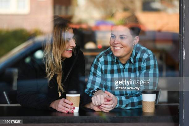 two women sitting in a cafe enjoying each others company. - gender stock pictures, royalty-free photos & images