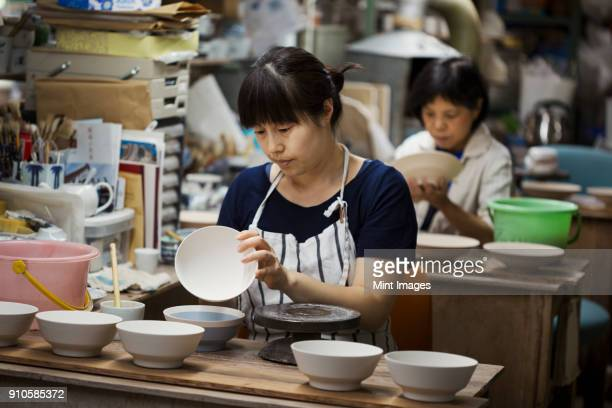 two women sitting in a workshop, working on japanese porcelain bowls. - porcelain stock photos and pictures