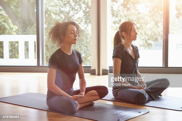 Two women sitting in a yoga class meditating