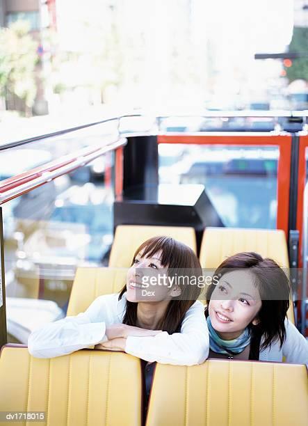Two Women Sitting in an Open Top Bus in Tokyo