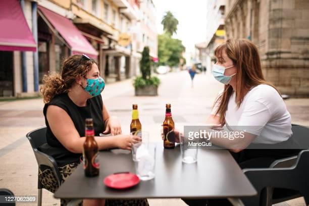 zwei frauen sitzen in einer bar-terrasse im freien mit gesichtsmasken - corona beer stock-fotos und bilder