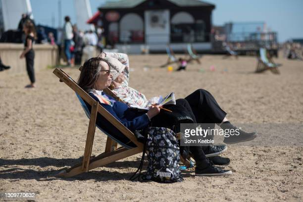 Two women sitting in deck chairs enjoy the warm weather on the beach on March 29, 2021 in Southend, England. Today the government eased its rules...