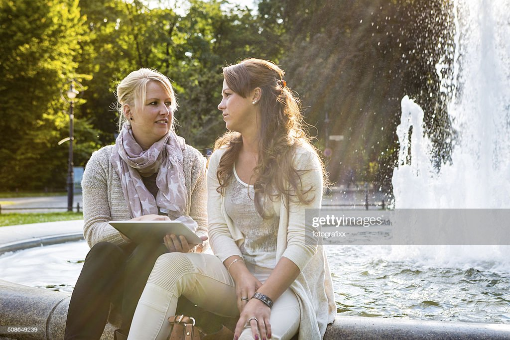two women sitting in front of fountain using digital tablet : Stock Photo