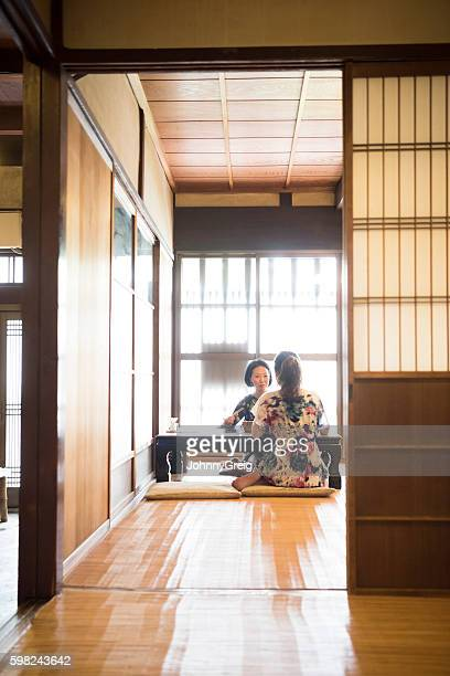 Two women sitting in Japanese restaurant, view through door