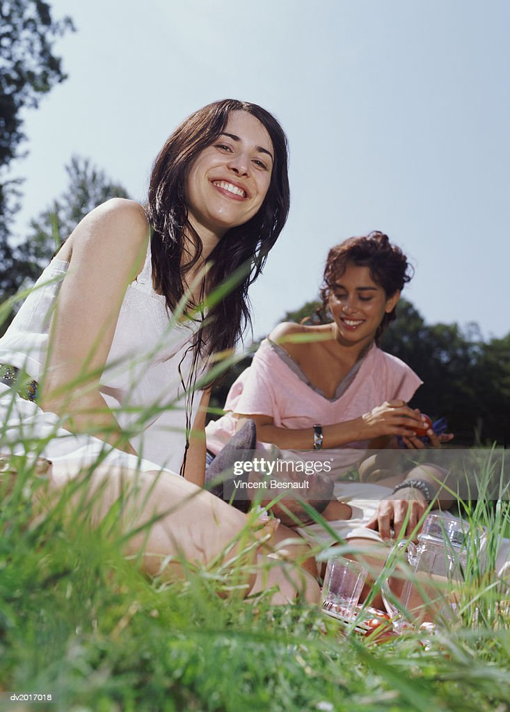 Two Women Sitting in the Grass Having a Picnic, Man Sleeping : Stock Photo