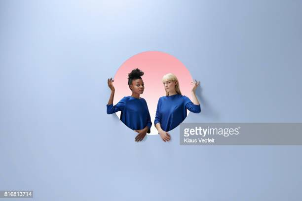 Two women sitting inside round opening in coloured wall