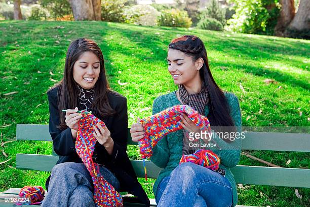 Two women sitting on a bench knitting