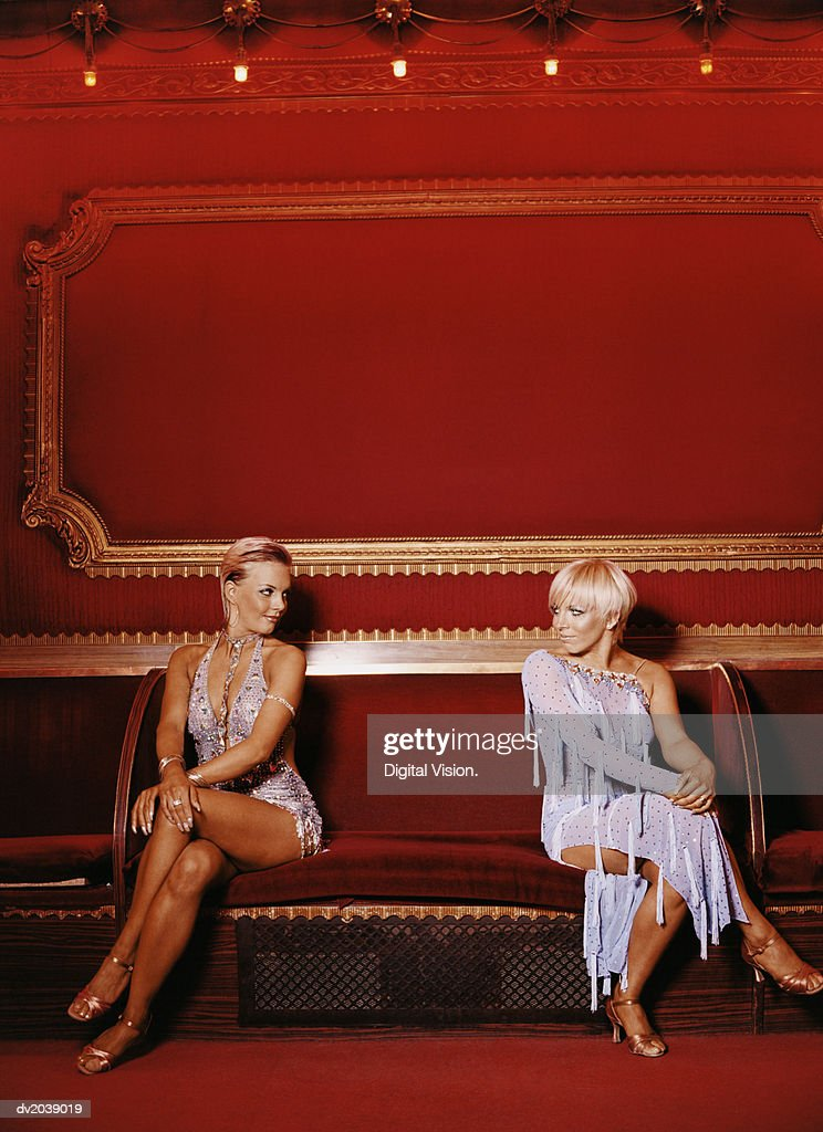 Two Women Sitting on a Bench Wearing Ballroom Dancing Dresses Looking at Each Other Face to Face : Stock Photo