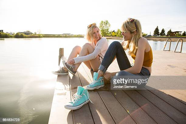 Two women sitting on a dock at sunset