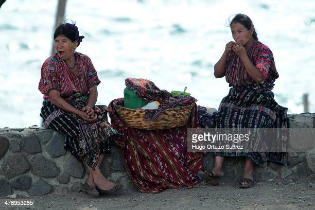 Two women sitting on a low wall waiting for customers. The sale of wool and cotton is very popular among tourists. Panajachel in the Guatemalan...