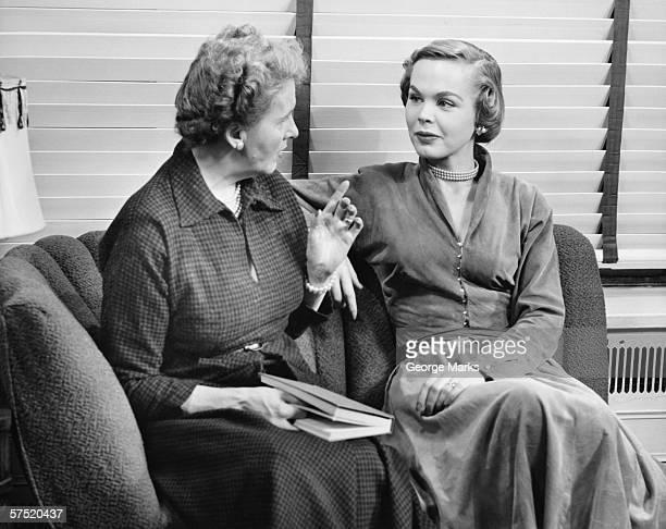 Two women sitting on couch, talking, (B&W)