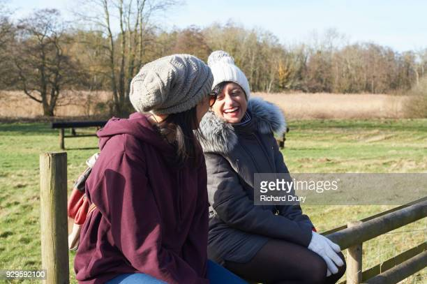 Two women sitting on country fence and talking