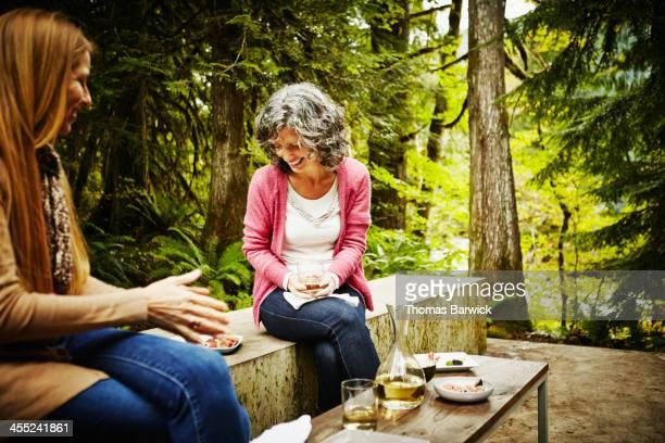 Two women sitting on patio having appetizers