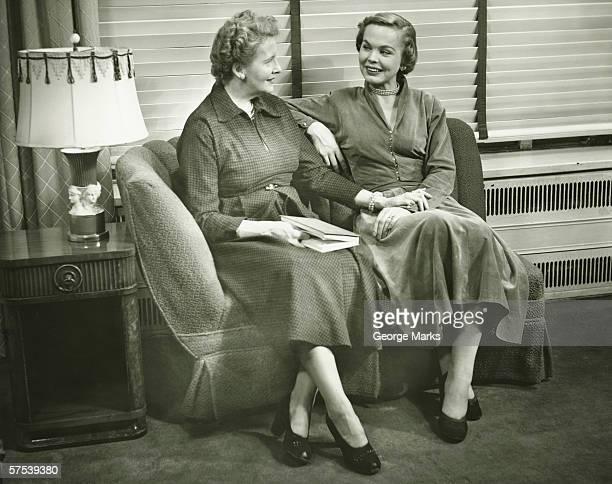 Two women sitting on sofa, talking, indoors, (B&W)