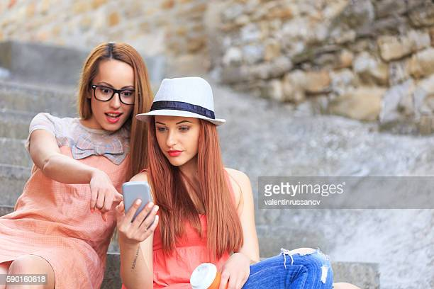 Two women sitting on stairs and using smart phone