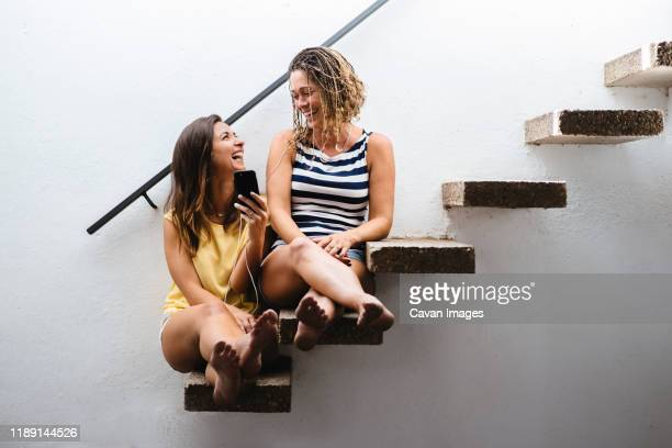 two women sitting on stairs laughing while listening to music. - jolies jambes photos et images de collection