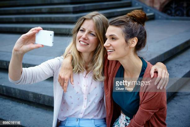 Two women sitting on stairs taking a selfie