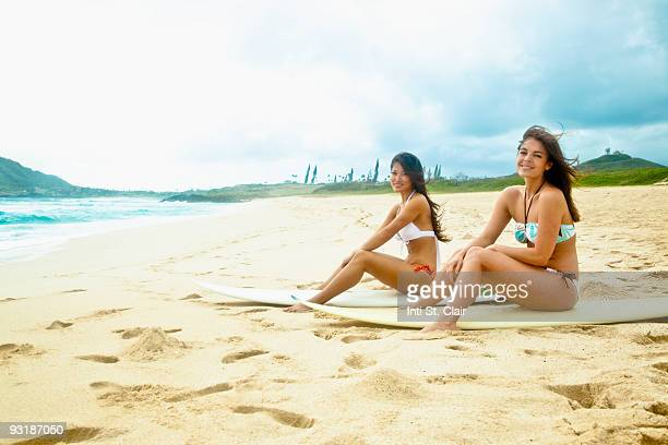 two women sitting on surfboards on the beach - kailua stock pictures, royalty-free photos & images