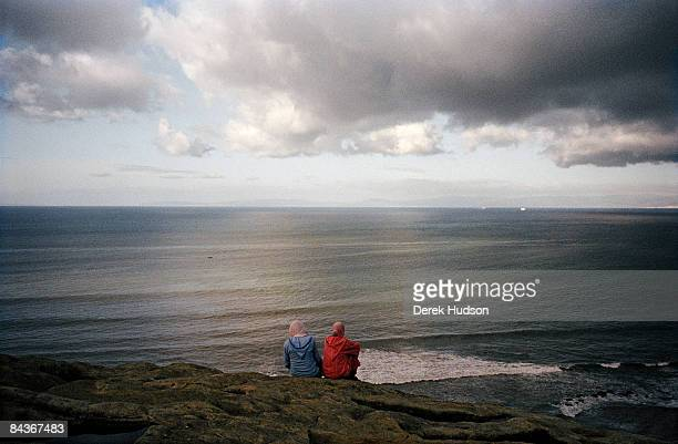 Two women sitting on the rock of the toms of the Phoenicians looking out towards the straits of Gibraltar from a viewpoint in the district of Marshan...