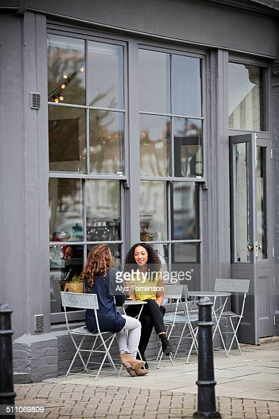 Two Women Sitting Outside at a Cafe