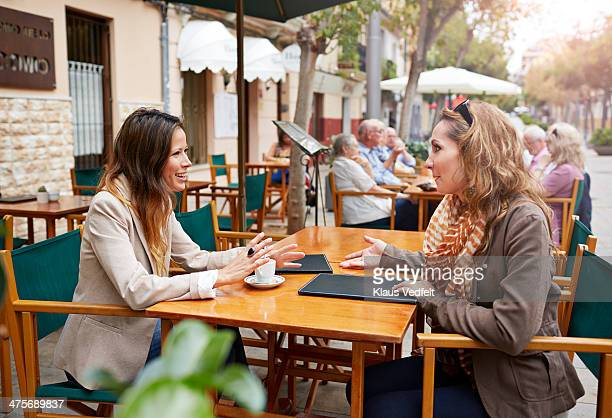 two women sitting outside café - klaus vedfelt mallorca stock pictures, royalty-free photos & images