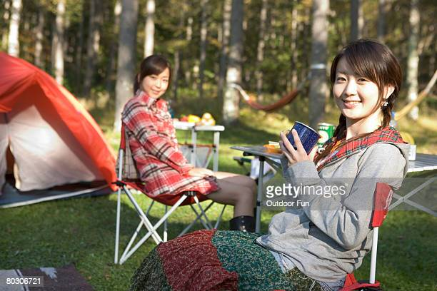 Two women sitting outside their tent