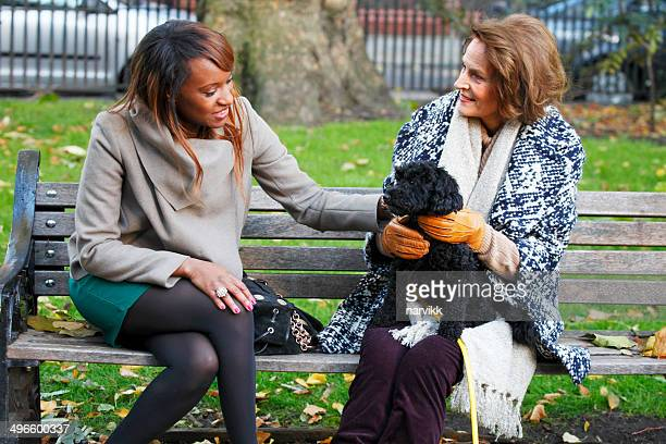 Two women sitting together on the bench in park