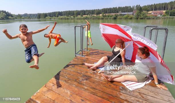 Two women sitting under parasols watch at three boys jumping into the water of a bathing lake in Bad Saulgau southern Germany where temperatures...
