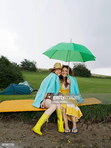 Two women sitting under umbrella