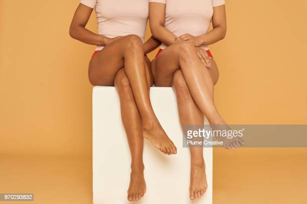 Two women sitting with legs crossed on white plinth