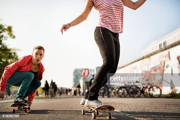two women skating with skateboards - berliner mauer stock-fotos und bilder