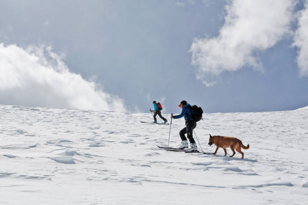 Two women ski up Mount Sopris with a dog in Colorado