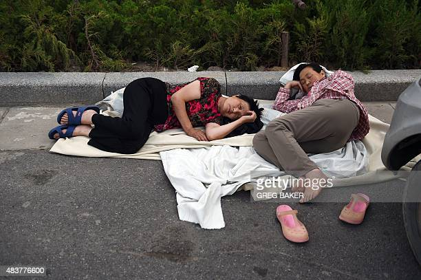 Two women sleep on the road outside a damaged residential building near the site of an explosion in Tianjin in northern China on August 13 2015 E...