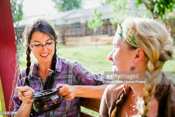 Two women smiling and talking while sitting on porch swing, one holding pot of soup