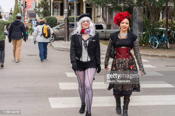 two women smiling wearing costumes in the street during the mardi gras celebration at new orleans carnival, louisiana, usa - mardi gras parade stock photos and pictures