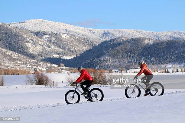 two women snow biking in colorado - steamboat springs colorado stock photos and pictures