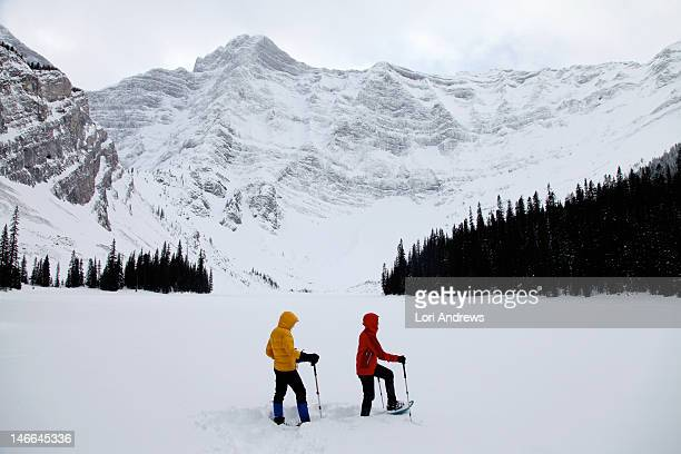 two women snowshoeing in snow covered mountains - kananaskis stock-fotos und bilder