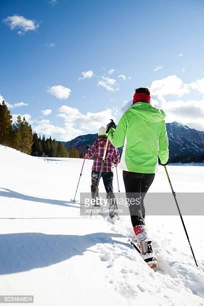 Two women snowshoeing on winter day, Bozeman, Montana, USA